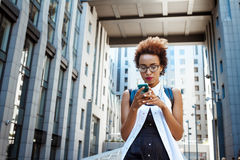 Young beautiful african girl looking at phone walking down city. Young beautiful african girl in glasses looking at phone walking down city. Fashion street Stock Photos