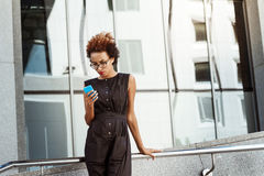 Young beautiful african girl looking at phone walking down city. Young beautiful african girl in glasses looking at phone walking down city. Fashion street Royalty Free Stock Image