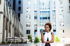 Young beautiful african girl looking at phone walking down city. Young beautiful african girl in glasses looking at phone walking down city. Fashion street Stock Images