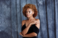 Young beautiful african girl posing over grey cloth background. Stock Photography
