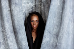 Young beautiful african girl posing, wrapping up  in grey cloth. Stock Images