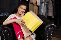 Young beautiful african girl sitting in shopping mall with buyings. Young beautiful african girl sitting in shopping mall with buyings, smiling stock image