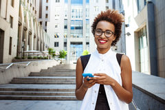 Young beautiful african girl smiling holding phone walking down city. Young beautiful african girl in glasses smiling holding phone walking down city. Fashion Royalty Free Stock Photos