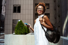 Young beautiful african girl smiling holding phone walking down city. Young beautiful african girl in glasses smiling holding phone walking down city. Fashion Royalty Free Stock Photography