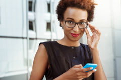 Young beautiful african girl smiling holding phone walking down city. Young beautiful african girl in glasses smiling looking at camera holding phone walking Royalty Free Stock Photography