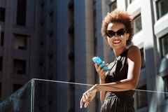 Young beautiful african girl smiling holding phone walking down city. Young beautiful african girl in sunglasses smiling looking at camera holding phone walking Royalty Free Stock Image