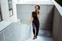Young beautiful african girl speaking on phone going up stairs. Young beautiful african girl in glasses speaking on phone going up stairs. Fashion street style Stock Photo
