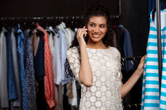 Young beautiful african girl speaking on phone in shopping mall. Royalty Free Stock Images