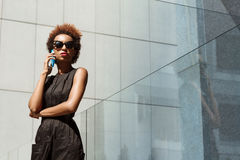Young beautiful african girl speaking on phone walking down city. Young beautiful african girl in sunglasses speaking on phone walking down city. Fashion street Stock Images