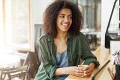 Young beautiful african girl student resting relaxing sitting in cafe smiling drinking coffee. Stock Photography