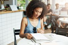 Young beautiful african girl student sitting in cafe smiling looking at magazine drinking coffee. Learning and education stock photo