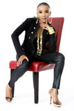 Young Beautiful African Woman Sitting on Red Chair. Wearing a Black Jacket, Golden Jewellery and Pink Lips, Fashion, Studio Shot, Isolated on White Background Stock Photography