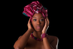 Young beautiful african woman wearing a traditional headscarf, I. Solated over black background Royalty Free Stock Photos