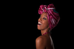 Young beautiful african woman wearing a traditional headscarf, I. Young beautiful african woman wearing a traditional headscarf,  over black background Stock Image