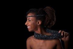 Young beautiful african woman wearing traditional jewelry, Isol. Young beautiful african woman wearing traditional jewelry, over black background royalty free stock photos