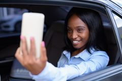 Young beautiful African Zulu businesswoman riding inside the car stock photography