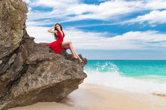 Young beautiful alone woman in red dress sitting on the rock on Royalty Free Stock Photos