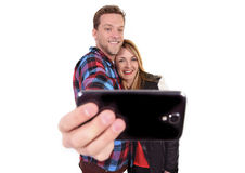 Young beautiful American couple in love taking romantic self portrait selfie photo together with mobile phone. Smiling happy wearing trendy clothes isolated on Royalty Free Stock Images