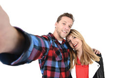 Young beautiful American couple in love taking romantic self portrait selfie photo together with mobile phone. Smiling happy wearing trendy clothes isolated on Stock Image