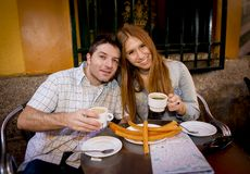 Young beautiful American tourist couple having spanish typical breakfast hot chocolate with churros smiling happy Royalty Free Stock Photo