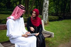 Young beautiful Arabian couple casual and hijab, Abaya, taking a selfie on the lawn in summer park. stock photos