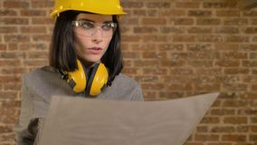 Young beautiful architect woman planning new project, pointing on something, brick building background stock footage