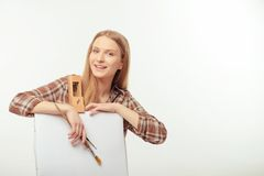 Young beautiful artist posing with a drawing easel Royalty Free Stock Image