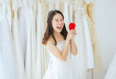 Young beautiful asian bride female in white dress with hands holding model heart red color,Happy and smiling. Young beautiful asian bride female in white dress royalty free stock image