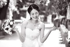 Asian bride rejoicing with bouquet in hand Royalty Free Stock Images