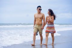 young beautiful Asian Chinese couple walking together holding hands on the beach happy in love Stock Images