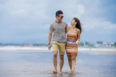 young beautiful and Asian Chinese romantic couple walking together embracing on the beach happy in love enjoying holidays Royalty Free Stock Photos