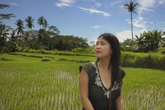 Young beautiful Asian Chinese tourist exploring jungle and rice field pad area in Bali Indonesia relaxed and happy enjoying holida Stock Image