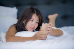 Young beautiful Asian Chinese woman with earpiece listening to music smiling happy lying on bed using internet on mobile phone Royalty Free Stock Photo