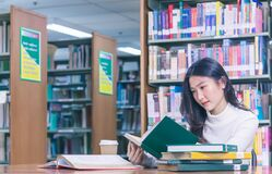 Free Young Beautiful Asian Female Student Portrait Sitting And Concentrate Studying Or Reading Textbook In University Library For Exams Royalty Free Stock Photos - 171050188