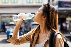 Female tourist drinking water in city of Bangkok, Thailand. Young beautiful Asian female tourist woman drinking water from plastic bottle in city of Bangkok royalty free stock photography