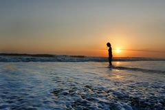 Young beautiful Asian girl alone at sea shore looking at orange sky sunset over ocean Royalty Free Stock Images