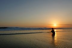 Young beautiful Asian girl alone at sea shore looking at orange sky sunset over ocean Royalty Free Stock Photography