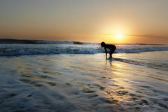 Young beautiful Asian girl alone at sea shore looking at orange sky sunset over ocean Stock Photos