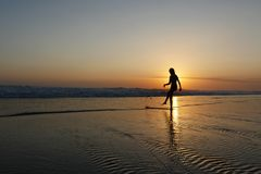 Young beautiful Asian girl alone at sea shore looking at orange sky sunset over ocean. At Indonesia Bali beach in freedom and meditation concept enjoy summer Royalty Free Stock Images
