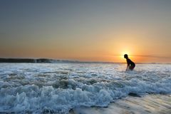 Young beautiful Asian girl alone at sea shore looking at orange sky sunset over ocean. At Indonesia Bali beach in freedom and meditation concept enjoy summer Stock Photos