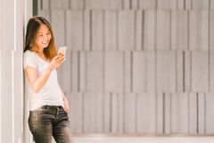 Young beautiful Asian girl or college student using smartphone and smiling. Modern lifestyle, communication technology concept stock photo