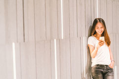 Young beautiful Asian girl or college student using smartphone and smiling. Modern lifestyle, mobile communication technology royalty free stock photos