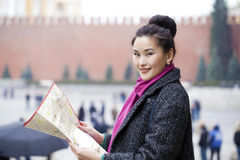 Young beautiful asian girl holding a tourist map of Moscow Stock Photos