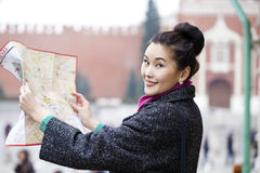 Young beautiful asian girl holding a tourist map of Moscow Royalty Free Stock Photos