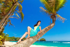 Young beautiful Asian  girl on the palm tree on a tropical beach Stock Photo