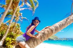 Young beautiful Asian girl on the palm tree on a tropical beach. Stock Images