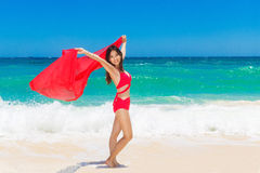 Young beautiful Asian girl with red cloth on the beach of a trop Stock Image