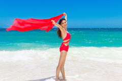 Young beautiful Asian girl with red cloth on the beach of a trop Stock Photos