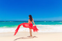 Young beautiful Asian girl with red cloth on the beach of a trop Stock Photography