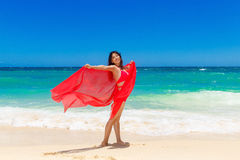 Young beautiful Asian girl with red cloth on the beach of a trop Stock Images